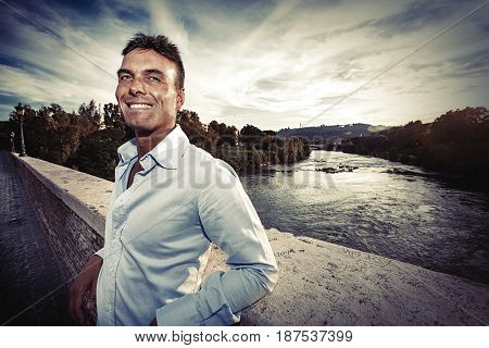 Beautiful smiling man outdoors. Tiber river from the bridge. A beautiful young Italian man posing outdoors on Milvian Bridge in the historic center of Rome, Italy. Blue shirt.