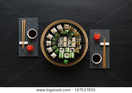 Japanese restaurant, sushi roll platter top view on black rustic wood background and black slate plates.. Set for two with chopsticks, ginger, soy, wasabi.