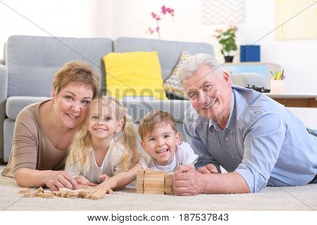 Happy senior couple and their grandchildren lying on floor and playing with wooden blocks