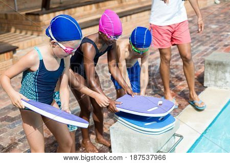 Low section of lifeguard assisting children for arranging kickboards at poolside