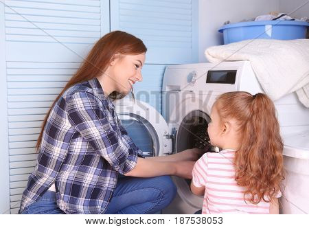 Daughter and mother doing laundry at home
