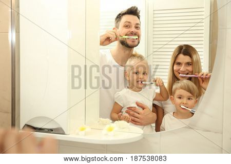 Young family with children brushing teeth and looking in mirror