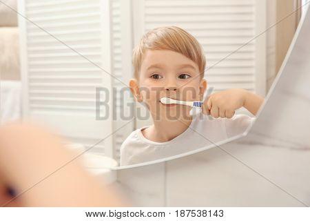 Cute little boy brushing teeth and looking in mirror