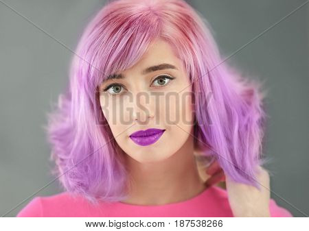 Beautiful young woman with dyed lilac hair and makeup on gray background