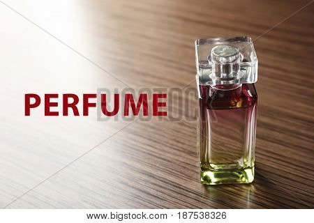 Bottle of perfume and text on wooden background
