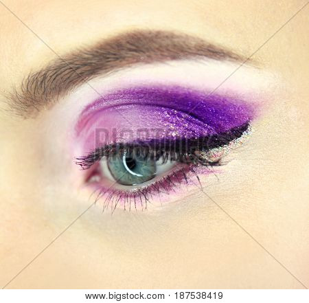 Female eye with lilac makeup, closeup