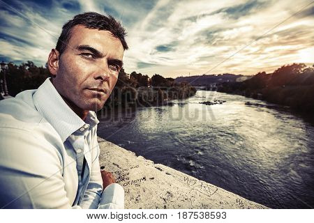 Lonely man looking suspicious. River at sunset. Italian handsome man on the bridge looking serious and confident attitude. Tiber river and the evening sky at sunset. Rome, Italy.