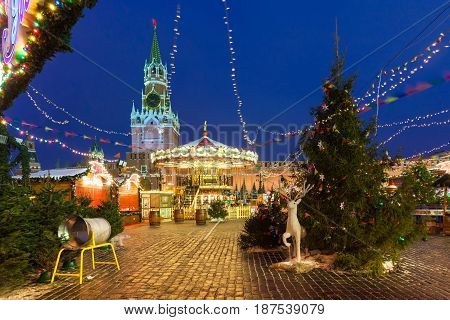 MOSCOW RUSSIA - DECEMBER 12: View of the Spasskaya Kremlin Tower with Christmas market on the foreground on December 12 2016 in Moscow Russia