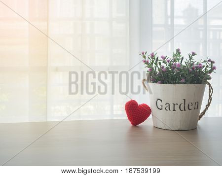 wood table with pink rose flower on flowerpot and red heart shape sign on blurry beautiful white drape window texture background concept of natural at home focus on flowerpot.