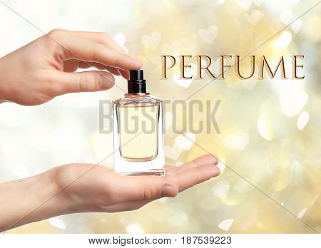 Woman holding perfume bottle on blurred background