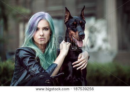 Trendy ideas. Young woman with mint color accent in hairstyle and dog outdoor