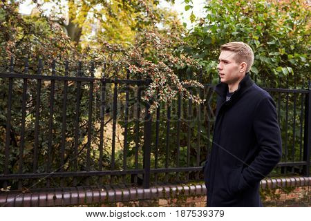 Young Man Walking Along Residential Street In Oxford