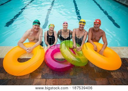 Portrait of senior swimmers with inflatable rings standing at poolside