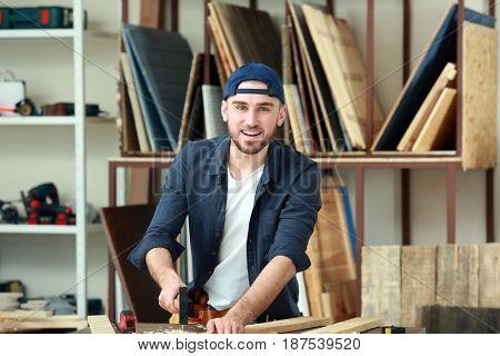 Handsome young carpenter in workshop