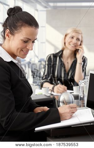 Happy businesswomen working at meeting table in office.