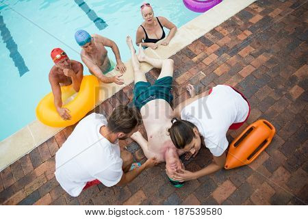 High angle view of friends looking at lifeguards saving unconscious senior man at poolside