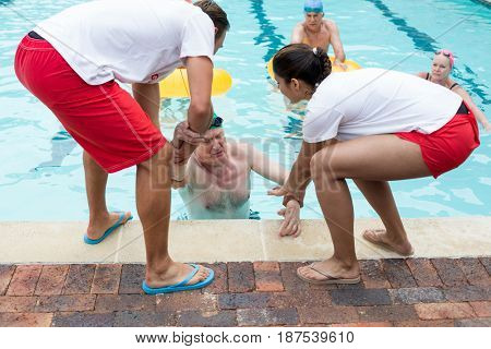 Male and female lifeguards helping Unconscious senior man in swimming pool
