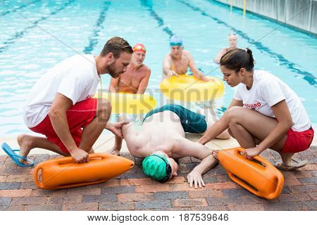 Male and female lifeguards helping unconscious senior man at poolside