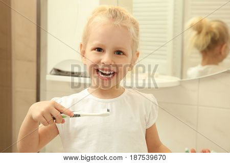 Happy little girl with beautiful smile holding toothbrush while standing in bathroom