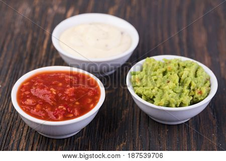 Bowls with sauces on white background