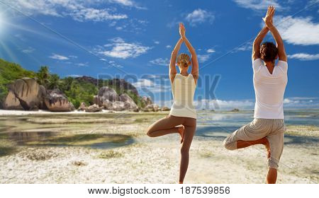 fitness, people and recreation concept - couple doing yoga in tree pose from back over exotic tropical beach background