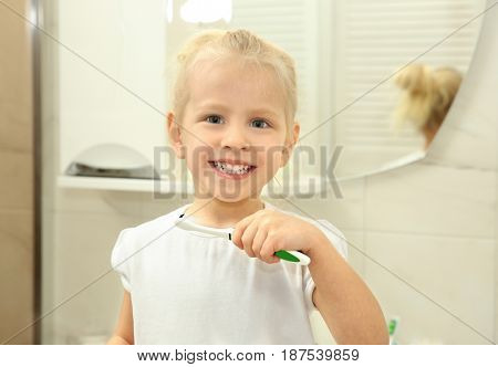 Little girl with beautiful smile holding toothbrush while standing in bathroom