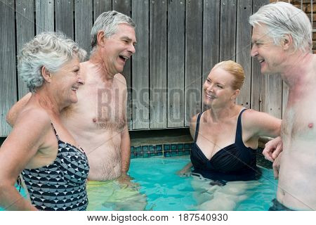 Group of swimmers talking while standing in swimming pool