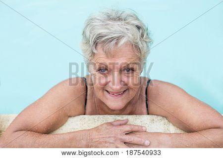 Portrait of senior woman leaning on poolside