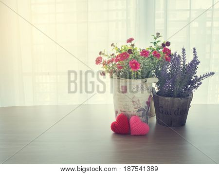 wood table with pink rose flower on flowerpot and red heart shape sign on blurry beautiful white drape window texture background.