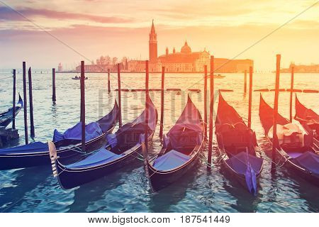 Pictorial view of blue gondolas in Venice Italy. Color toning effect has been applied.