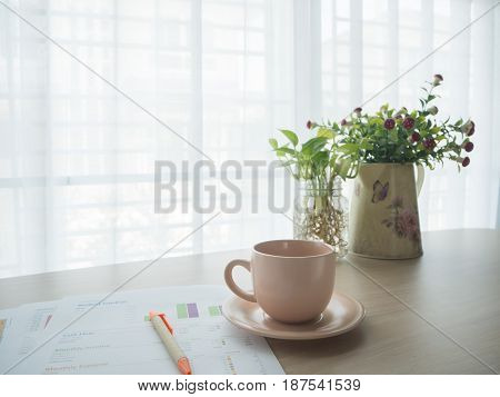 wood table with coffee cup blank screen notepad paper green betel leaf glass vase on blurry beautiful white drape window texture background.
