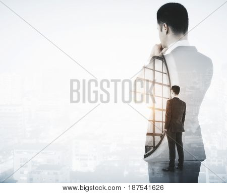 Back view of young businessman looking into the distance on light city background with copy space. Future concept. Double exposure