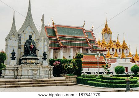 View From A Park With The Statue Of The King Of Thailand And The Golden Mountain Temple At The Back