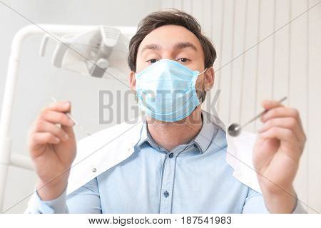 Dentist with mirror and periodontal explorer in clinic