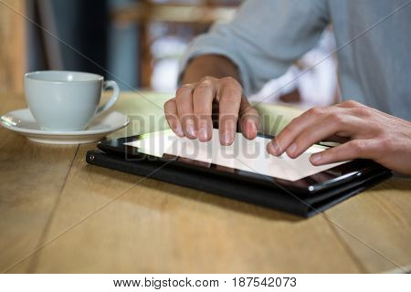 Cropped image of young man using digital tablet at table in coffee shop