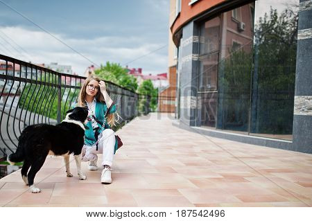 Trendy Girl At Glasses And Ripped Jeans With Russo-european Laika (husky) Dog On A Leash, Against Bu