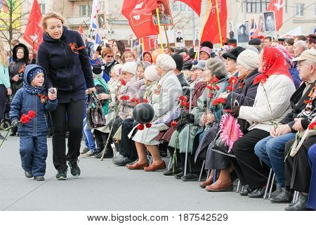Kirishi, Russia - 9 May, People with flowers at a rally, 9 May, 2017. Holding a festive rally dedicated to the Victory Day.