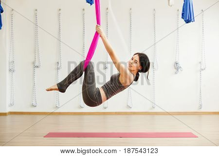 Smiling girl in silk hammock building strength and flexibility of her body. Aerial yoga exercise or antigravity yoga indoors, woman meditating in sport studio or gym side view