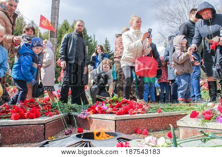 Kirishi, Russia - 9 May, Adults and children at the Eternal Flame, 9 May, 2017. Laying wreaths and flowers in memory of the fallen at the Eternal Flame.