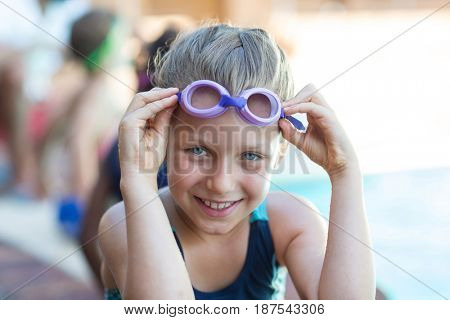 Portrait of smiling little girl holding swimming goggles