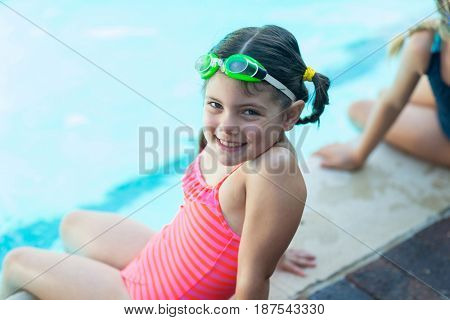 Portrait of cute little girl resting at poolside