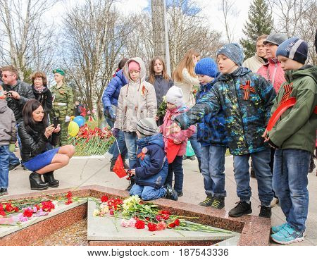 Kirishi, Russia - 9 May, A teenager throws a coin into the Eternal Flame, 9 May, 2017. Laying wreaths and flowers in memory of the fallen at the Eternal Flame.