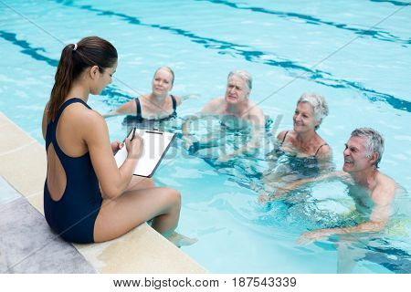 High angle view of female instructor writing while instructing senior swimmers at poolside