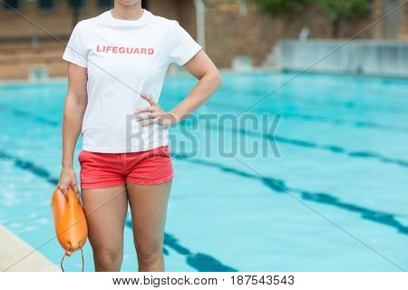 Mid section of female lifeguard holding rescue can at poolside