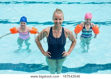 Portrait of female swimming trainer with girls in swimming pool