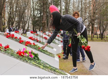Kirishi, Russia - 9 May, Girls put red roses on monuments, 9 May, 2017. Laying wreaths and flowers in memory of the fallen at the Eternal Flame.