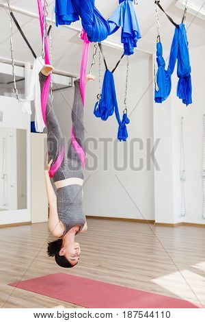 Aerial yoga exercise or antigravity yoga indoor, woman meditating in sport studio or gym. Girl hanging upside down in relaxed pose