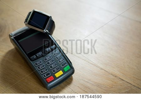 Close-up of smart watch and credit card reader on table in coffee shop