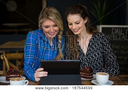 Smiling young women using digital tablet in coffee shop