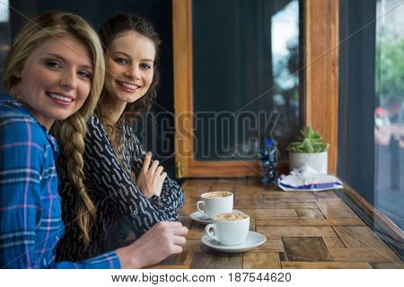 Portrait of smiling young woman with coffee cups on table in cafe